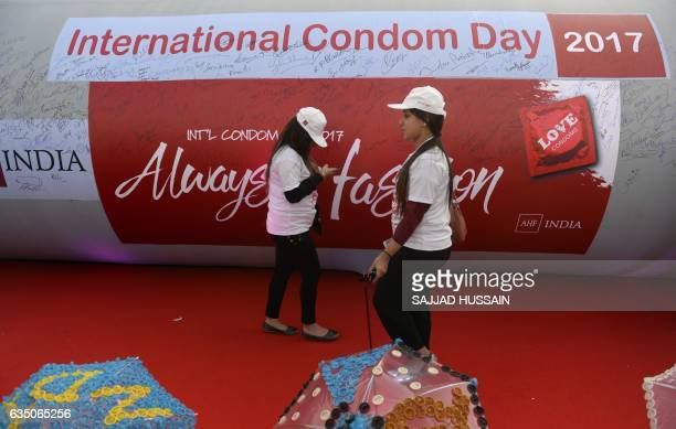 Volunteers walks in front of an inflatable condom shaped balloon during an event to mark International Condom Day in New Delhi on February 13 2017...