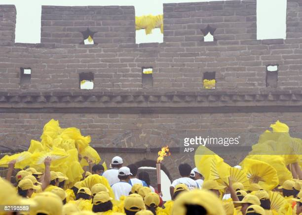 Volunteers watch as the Olympic torch is carried along a section of the Great Wall in Badaling outside Beijing on August 07 2008 a day before the...