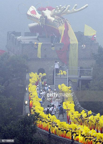 Volunteers watch as the Olympic torch relay procedes along a section of the Great Wall in Badaling outside Beijing on August 07 2008 a day before the...