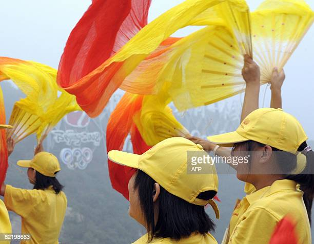 Volunteers wave banners during a ceremony as the Olympic torch relay procedes along a section of the Great Wall in Badaling outside Beijing on August...