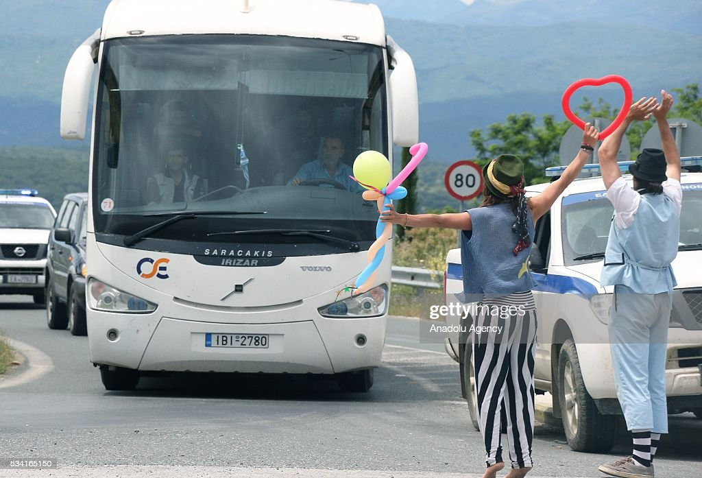 Volunteers wave to refugees onboard a bus, as Greek police evacuate the makeshift refugee camp at the Greek-Macedonian border near the northern Greek village of Idomeni on May 25, 2016.