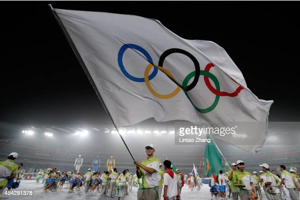 A volunteers waves the Olympic flag during the Closing Ceremony of Nanjing 2014 Summer Youth Olympic Games at the Nanjing Olympic Sports Centre on...