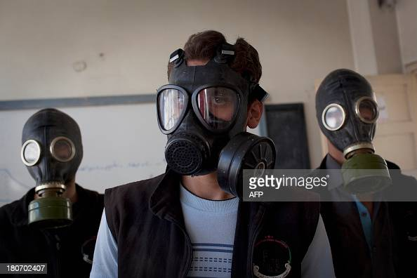 Volunteers wear gas masks during a class on how to respond to a chemical attack in the northern Syrian city of Aleppo on September 15 2013 For two...