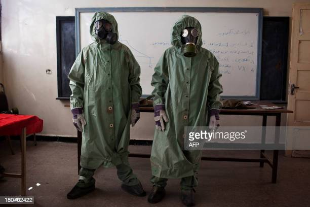 Volunteers wear protective gear during a class of how to respond to a chemical attack in the northern Syrian city of Aleppo on September 15 2013 For...