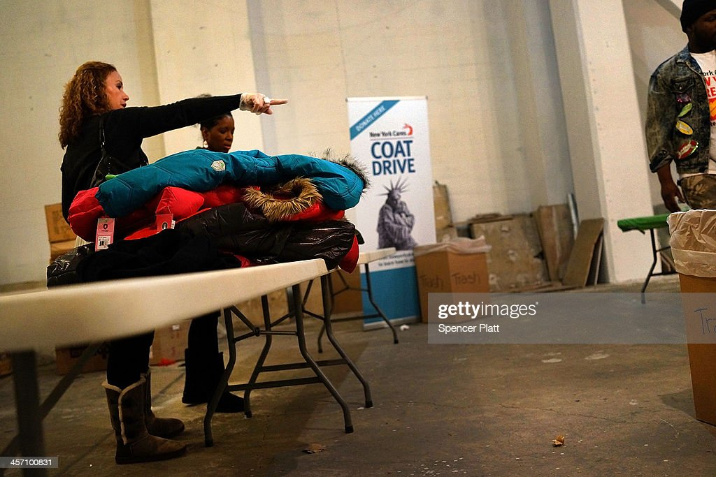 Volunteers with BNP Paribas sort coats at the annual New York Cares coat drive on December 16 2013 in New York CityThe drive for winter jackets for...