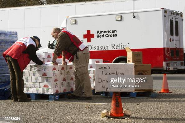 Volunteers with the American Red Cross review their notes as they distribute relief supplies to Hurricane Sandy victims November 5 in Ocean County...