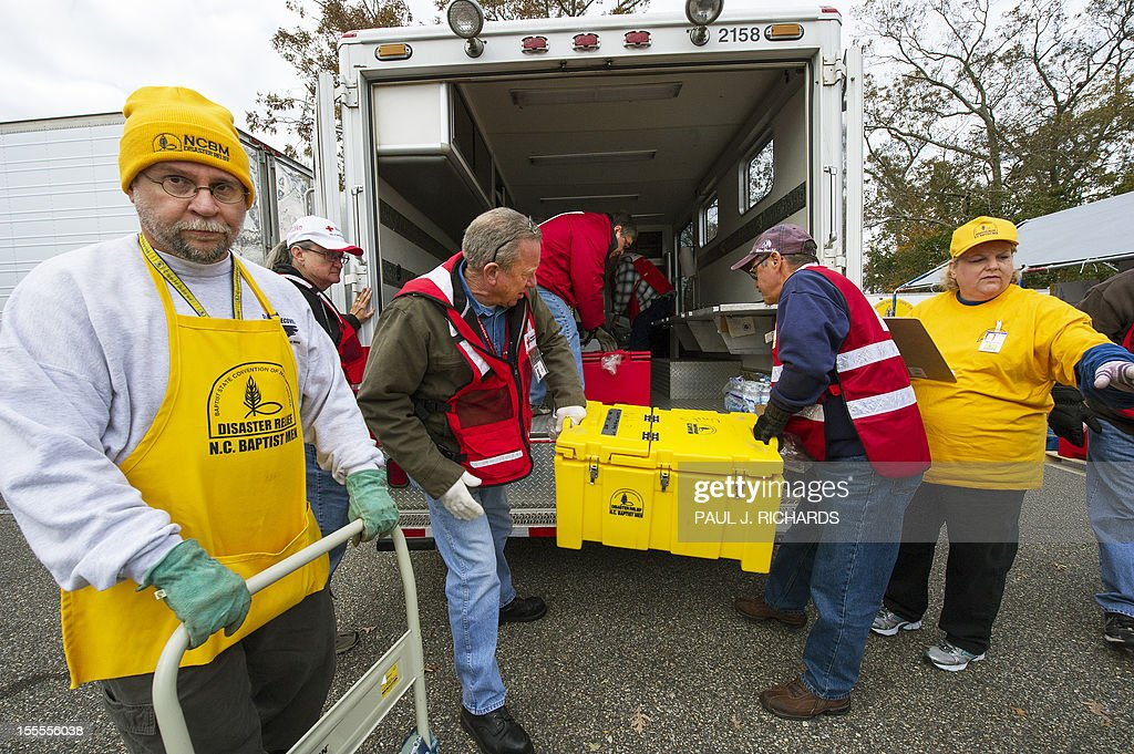 Volunteers with the North Carolina Baptist Men disaster relief(in yellow) and the American Red Cross(in red) load up fresh hot meals of Ribs, Sweet Potatoes, and Hush Puppies, that they will distribute to Hurricane Sandy victims November 5, 2012, in Ocean County, New Jersey. The two groups have a large staging area in a church parking lot and smaller Red Cross vans shuttle in food on 'search and feed' missions to victims in devastated costal areas. AFP PHOTO/Paul J. Richards