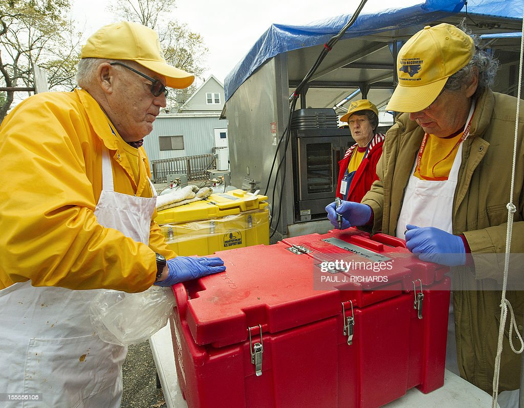 Volunteers with the North Carolina Baptist Men disaster relief and the American Red Cross load up fresh hot meals of Ribs, Sweet Potatoes, and Hush Puppies, that they will distribute to Hurricane Sandy victims November 5, 2012, in Ocean County, New Jersey. The two groups have a large staging area in a church parking lot and smaller Red Cross vans shuttle in food on 'search and feed' missions to victims in devastated costal areas. AFP PHOTO/Paul J. Richards