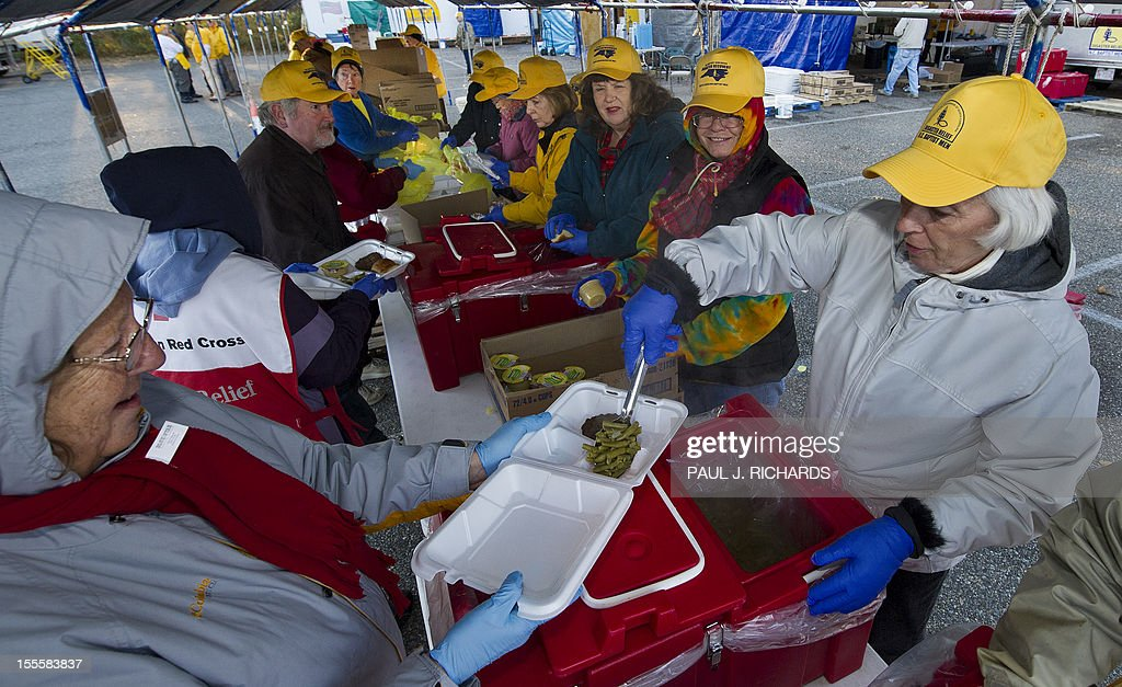 Volunteers with the North Carolina Baptist Men's Disaster Relief (in yellow caps) work with volunteers from the American Red Cross (in red) preparing hot meals on an assembly line for distribution to Hurricane Sandy victims November 5, 2012 in a variety of cities in Ocean County, New Jersey. The two groups have a large staging area in the First Baptist Church of Toms River parking lot and Red Cross vans shuttle in food on 'search and feed' missions to victims in devastated costal areas. They also allow anyone that is hungry to drive up for a hot meal. AFP PHOTO/Paul J. Richards