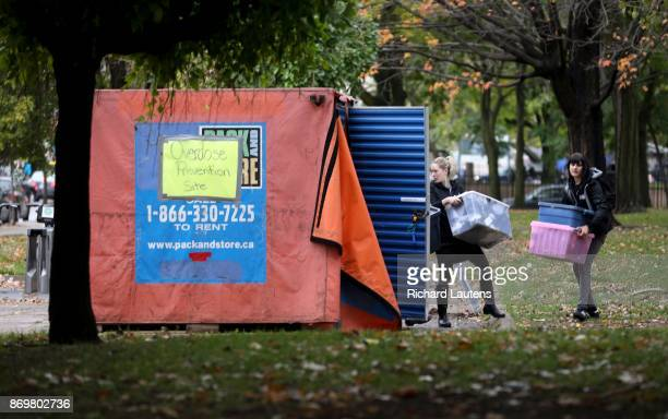 Volunteers with the Toronto Overdose Prevention Society carry supplies to the tents The Ontario EMAT team went to Moss Park on Thursday afternoon to...