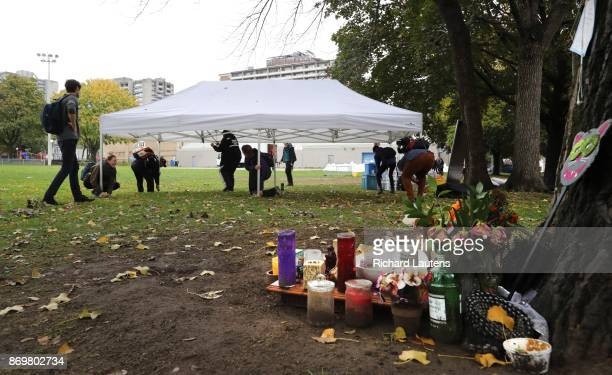 Volunteers with the Toronto Overdose Prevention Society erect their usual portable tent in Moss Park next to a makeshift memorial under a tree The...