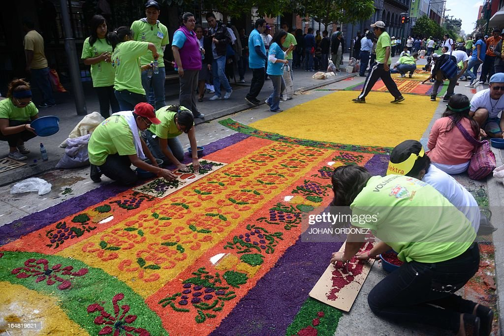 Volunteers work on the making of a 1,400 meters carpet of flowers and colored sawdust, made by municipal employees and volunteers in an attempt to set a Guinness World Record for the longest carpet of the world, in Guatemala City on March 28, 2013. These carpets are traditionally made during Hoy Week each year. AFP PHOTO / Johan ORDONEZ