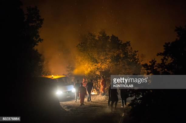 Volunteers work to extinguish a vast fire in Sila in Calabria southern Italy