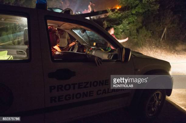 Volunteers work to extinguish a vast fire in Sila with fire truck in Calabria southern Italy