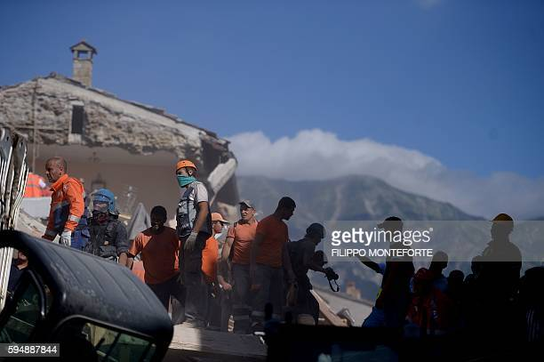 TOPSHOT Volunteers work to move rubble and debris during search and rescue operations in Amatrice on August 24 2016 after a powerful earthquake...