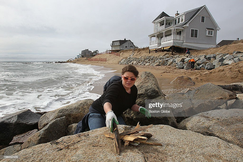 Volunteers worked with homeowners, local businesses, and local and state agencies to come together to assist in the clean up and repair to Plum Island beaches. Ashley Ashmead, of New Ipswich, New Hampshire, used to come to Plum Island as a child. She picks debris out of a wall of rocks.