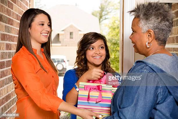 Freiwillige: Junge Erwachsene mit Geschenk senior Frau zu Hause fühlen.