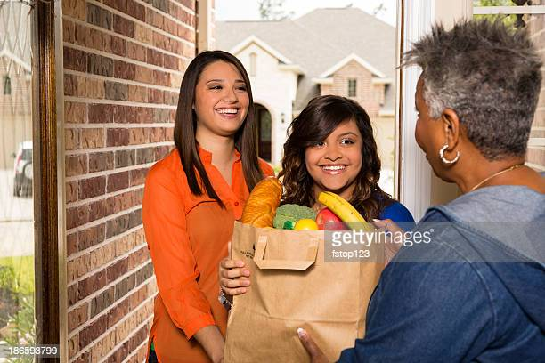 Volunteers:  Young adults bring groceries to senior woman.