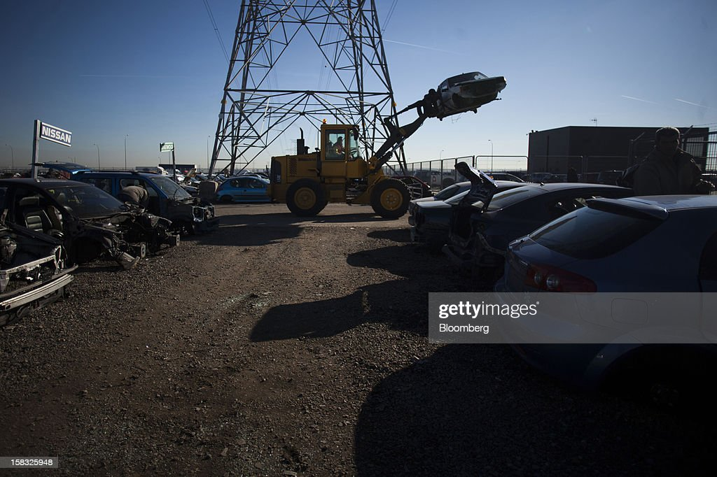 A Volvo front-loader moves a scrapped automobile across the yard of the Desguaces La Torre scrapyard in Madrid, Spain, on Thursday, Dec. 13, 2012. Spain has completed the debt sales it planned for this year and started raising funds for 2013, buying time for Prime Minister Mariano Rajoy as he decides whether to seek a European bailout. Photographer: Angel Navarrete/Bloomberg via Getty Images