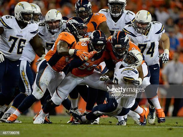 Von Miller of the Denver Broncos Sylvester Williams of the Denver Broncos and Nate Irving of the Denver Broncos stop Branden Oliver of the San Diego...