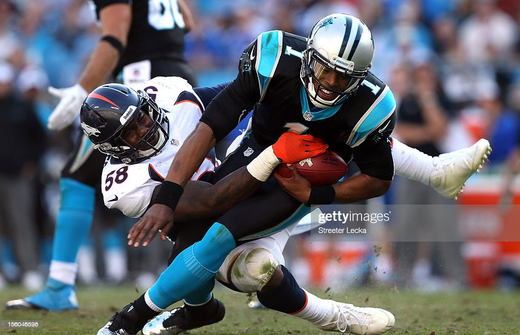 Von Miller #58 of the Denver Broncos tackles Cam Newton #1 of the Carolina Panthers during their game at Bank of America Stadium on November 11, 2012 in Charlotte, North Carolina.