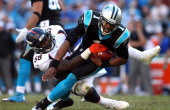Von Miller of the Denver Broncos tackles Cam Newton of the Carolina Panthers during their game at Bank of America Stadium on November 11 2012 in...