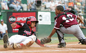 Vonn Fe'ao of the Northwest slides home safely past Willie Rifaela in the sixth inning during the Championship Game of the Little League World Series...