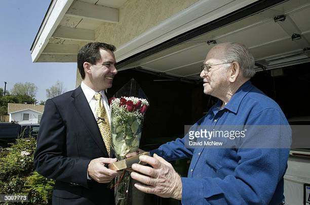 Vonscom president and CEO Mitch Rhodes hands chocolate and flowers to customer George Halpern on the first day of grocery homedelivery service since...