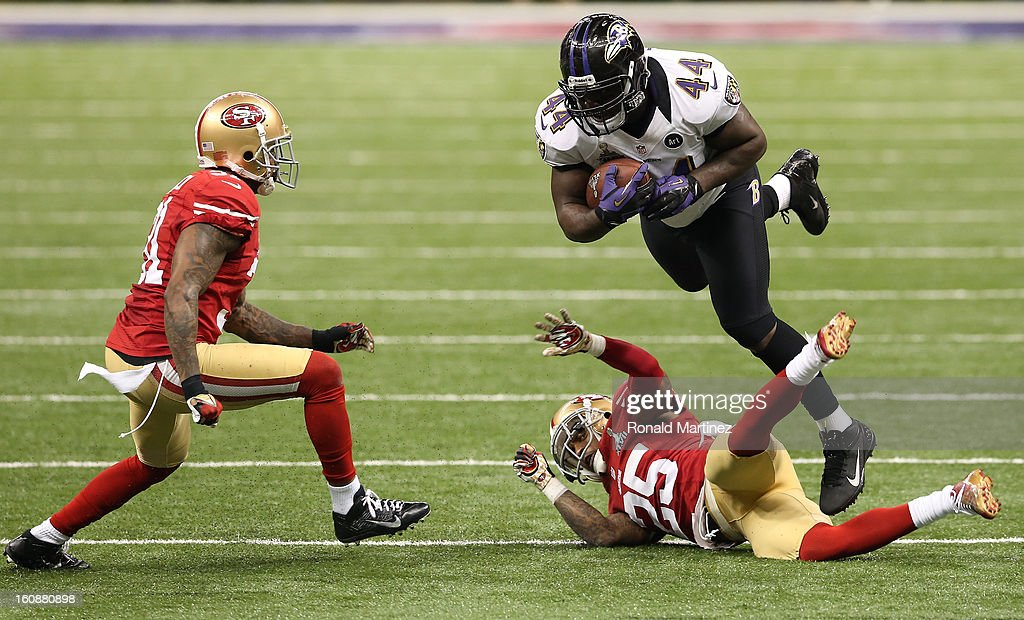 Vonta Leach of the Baltimore Ravens runs with the ball against Tarell Brown and Donte Whitner of the San Francisco 49ers during Super Bowl XLVII at...