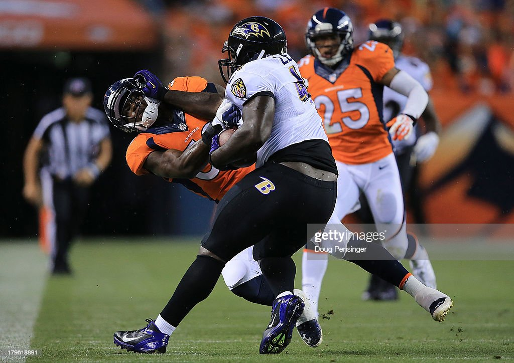 Vonta Leach of the Baltimore Ravens stiffarms Danny Trevathan of the Denver Broncos as he runs with the ball in the first quarter during the game at...