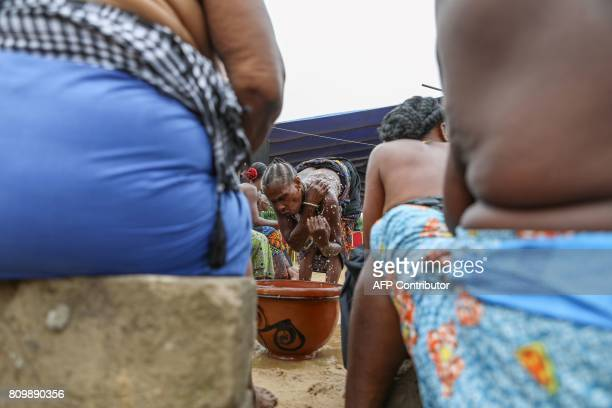 A voodoo adept splashes water during a purification ceremony in Be a working class district in Lome on July 7 2017 Roughly a hundred between...