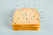 still life photography of a quirky soft bread stacked and used as a voodoo doll on a blue and minimal background