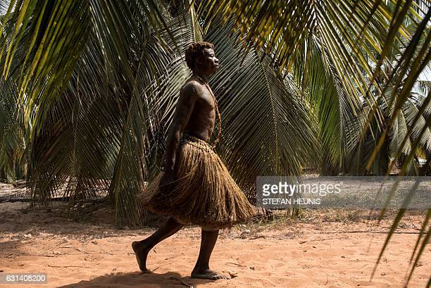 A Voodoo devotee walks through palm tree plantation on his way to the annual Voodoo Festival on January 10 2017 in Ouidah Officially declared a...