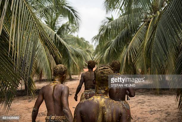 Voodoo devotees walk through a palm tree plantation on their way to the annual Voodoo Festival on January 10 2017 in Ouidah Officially declared a...