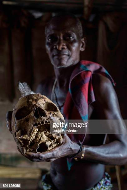 Voodoo priest showing a skull supposed to have belonged to a man killed by a lightning bolt According to voodoo tradition evildoers are killed by...