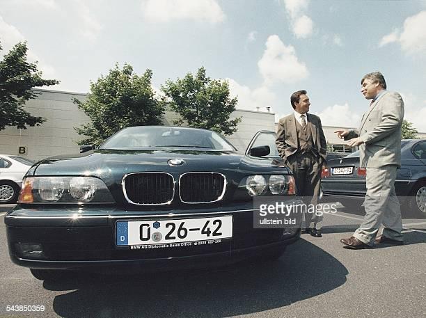 Vor einem PKW des Herstellers BMW stehen zwei Männer in Anzügen und verhandeln Das Nummernschild des Fahrzeuges trägt den Zusatz 'BMW AG Diplomatic...