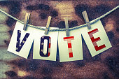 The word VOTE stamped on card stock hanging from old twine and clothes pins over a rusty vintage background.