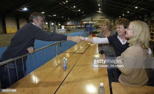 Vote counters shake hands with Sinn Fein leader Gerry Adams as counting continues in the local and European elections at the RDS in Dublin today