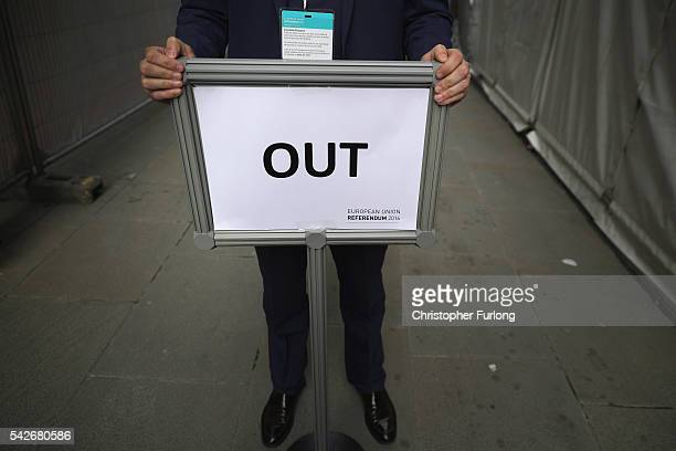 Vote Leave supporter grasps the 'out' exit sign directing media and guests away from the announcement of the final voting results of the EU...