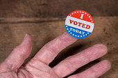 I Voted Today sticker on senior caucasian mans finger on rustic rural wooden table