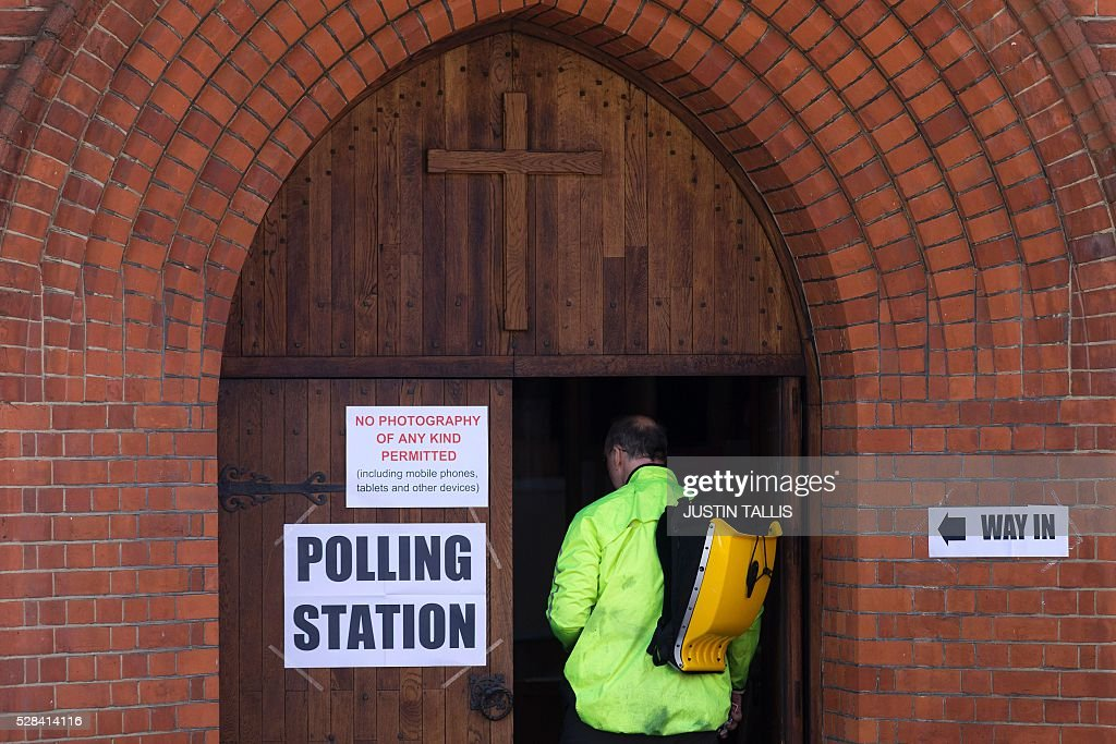 A voter arrives at a Polling Station in a church in south London on May 5, 2016, to cast their ballot papers. Londoners go to the polls on Thursday to elect their new mayor following a bitter campaign between the two leading candidates Labour's Sadiq Khan, and the Conservatives' Zac Goldsmith, that stayed ugly to the very end. While London chooses a new mayor, there are also elections to the Scottish, Welsh and Northern Irish assemblies, and 124 local authorities scattered across England. / AFP / JUSTIN