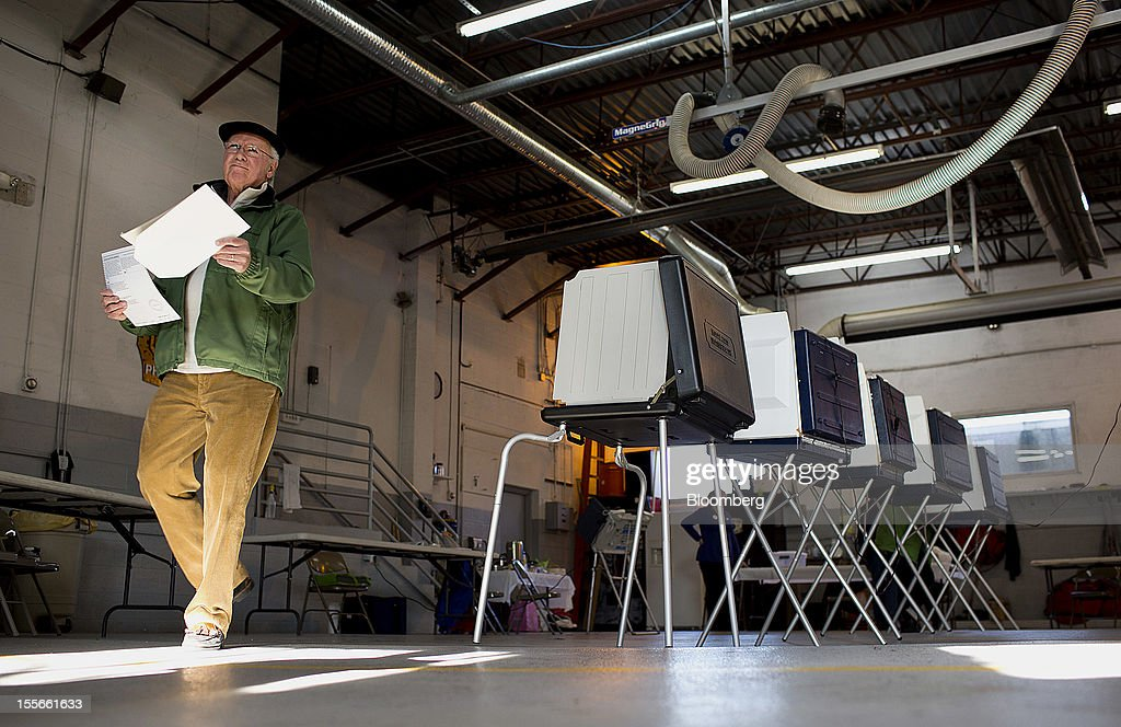A voter carries his ballot at the Philomont Firehouse polling location in Philomont, Virginia, U.S., on Tuesday, Nov. 6, 2012. U.S. President Obama is seeking to overcome the drag of high unemployment and economic weakness that has frustrated predecessors' re-election bids, while his Republican rival Mitt Romney reaches for an upset to propel him beyond his party's standing and swamp an electoral map stacked against him on the final day of the presidential race. Photographer: Joshua Roberts/Bloomberg via Getty Images