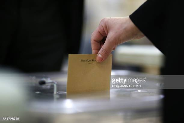 TOPSHOT A voter casts a ballot at a polling station in Pantin northeast of Paris on April 23 2017 during the first round of the presidential election...