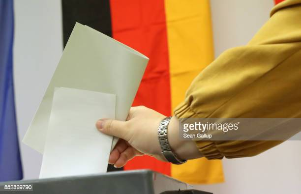A voter casts her ballot at a polling station during German federal elections on September 24 2017 in Berlin Germany German Chancellor and Christian...