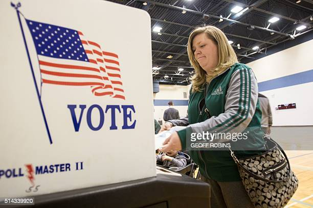 A voter casts her ballot for the Michigan presidential primary at a polling station in Warren Michigan March 8 2016 US voters cast ballots in White...