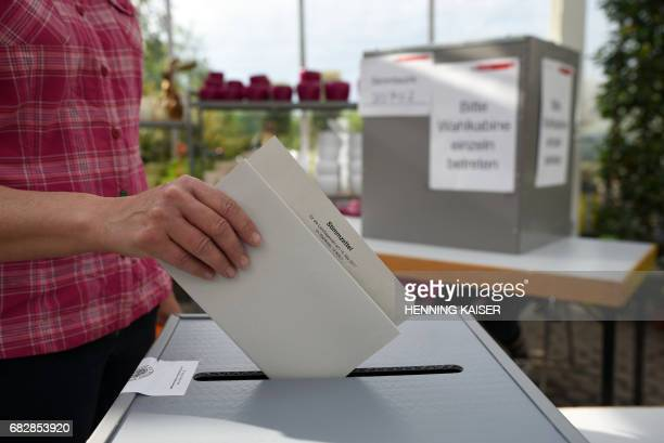 A voter casts her ballot in a gardening center on May 14 2017 in the western town of Cologne during North RhineWestphalia state elections About 131...