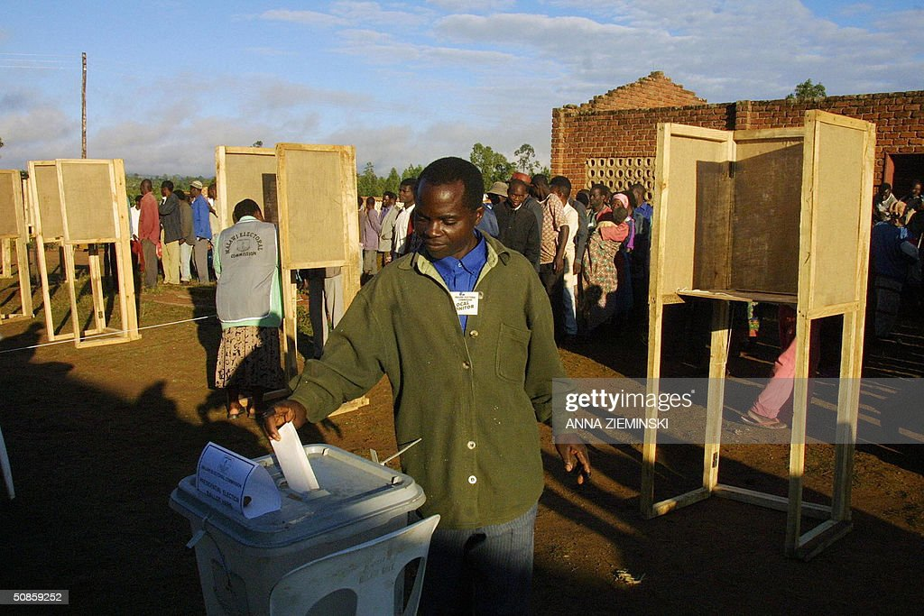 A voter casts his ballot as voters wait in line at a polling station at the Goliati Primary School in Thyolo district, about 50 kms outside Blantyre 20 May 2004. Malawians went to the polls 20 may in the country's third democratic general elections.