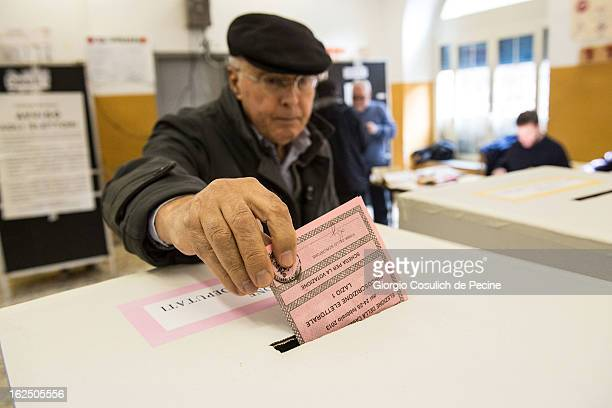 A voter casts his ballot at a polling station on February 24 2013 in Rome Italy Italians are heading to the polls today to vote in the elections as...