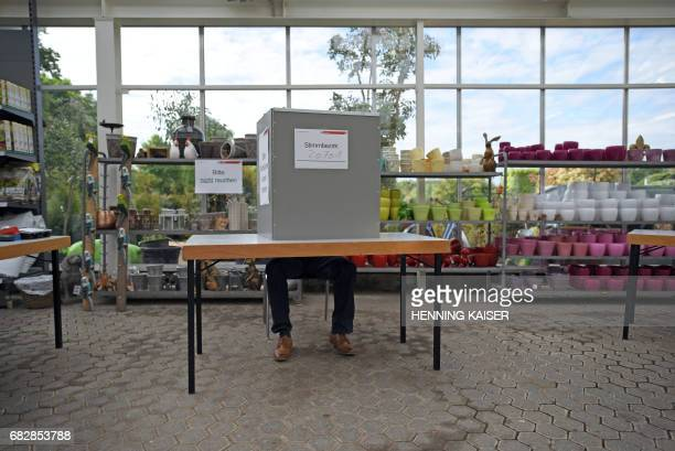 A voter casts his ballot in a gardening center on May 14 2017 in the western town of Cologne during North RhineWestphalia state elections About 131...