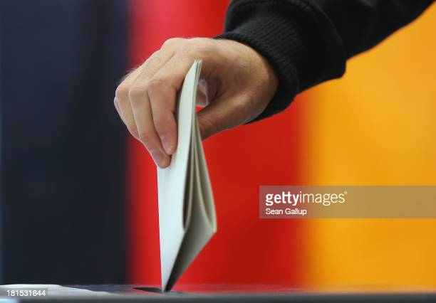 A voter casts his ballot in German federal elections as a German flag hangs behind on September 22 2013 in Berlin Germany Germany is holding federal...